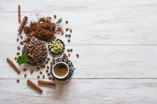 Tasse de café, grains de café, cannelle et cardamome avec poudre moulue sur table en bois blanc. vue de dessus.
