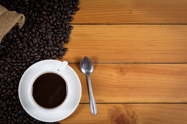 Tasse de café et grains de café dans un sac sur bois