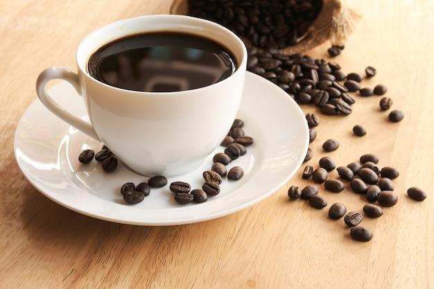 Tasse de café et grains de café dans le sac sur fond en bois