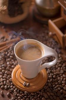 Tasse de café et de grains de café dans un sac sur une surface sombre, vue du dessus