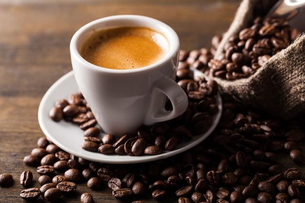 Tasse de café et grains de café dispersés sur fond de bois