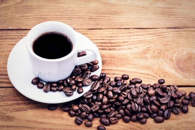 Une tasse de café et des grains de café dispersés.