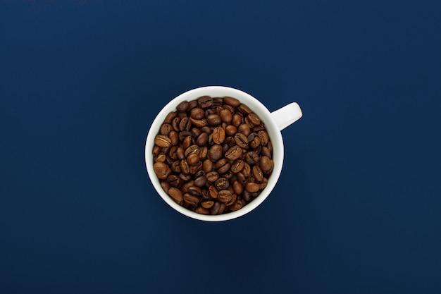 Tasse à café avec des grains de café sur fond bleu.
