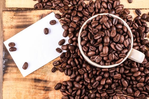 Tasse à café et grains de café sur fond en bois. avec une note blanche