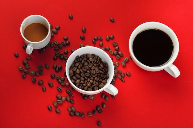 Tasse à café avec des grains de café sur fond rouge.