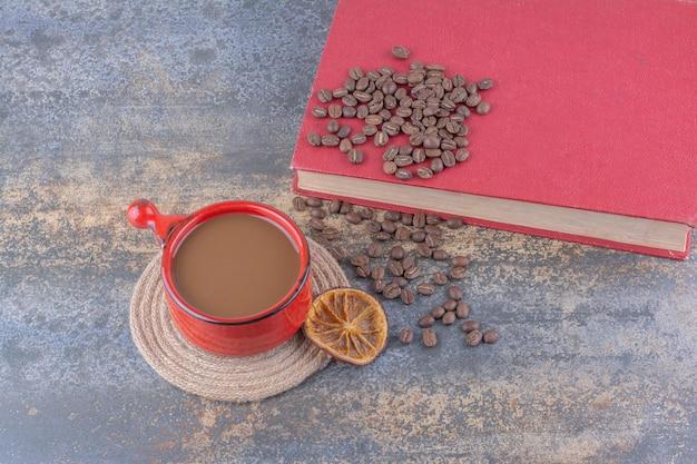 Tasse de café, grains de café et livre sur une surface en marbre. photo de haute qualité