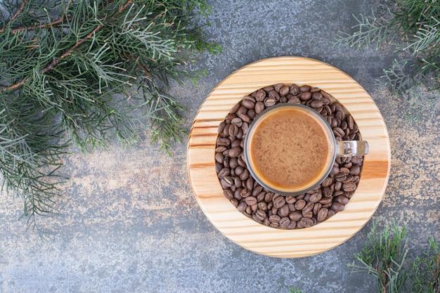 Une tasse de café avec des grains de café sur une planche de bois.