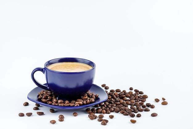Tasse de café et de grains de café sur un plateau isolé