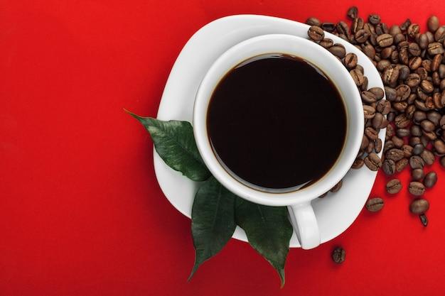 Tasse à café avec grains de café sur le rouge