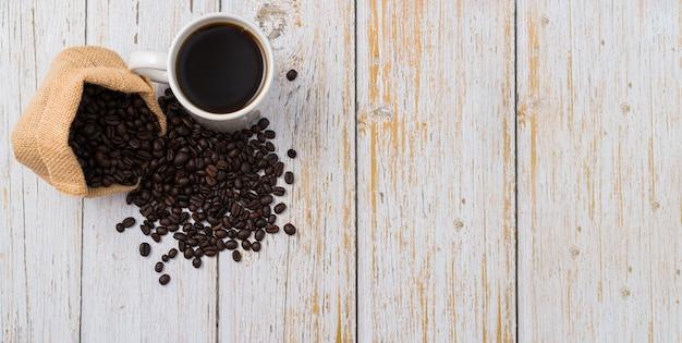 Tasse à café et grains de café sur table en bois