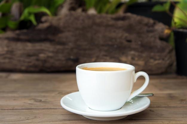 Tasse de café avec des grains de café sur la table en bois