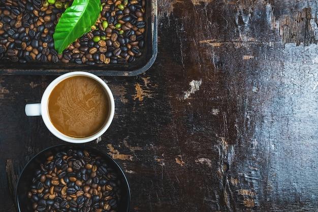 Une tasse de café et des grains de café sur une table en bois