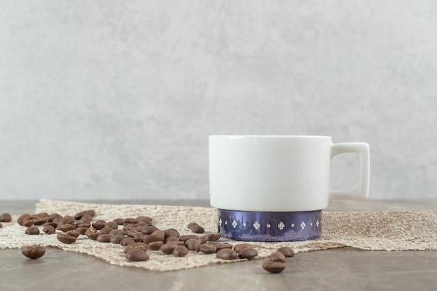 Tasse à café et grains de café sur table en marbre.