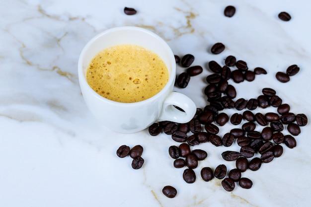 Tasse à café et grains de café sur la table en marbre