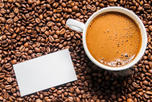 Tasse à café et grains de café sur la table, vue de dessus, café amoureux, grains de café brun isolés sur fond blanc, tasse de café chaud avec des grains de café