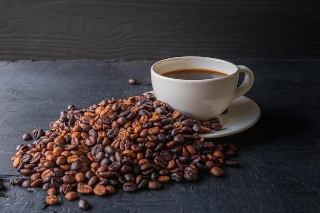 Tasse à café et grains de café torréfiés sur fond noir