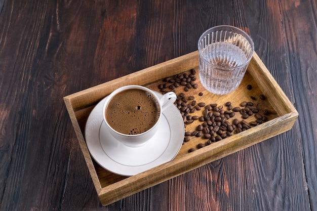 Tasse de café, grains de café et verre d'eau dans une boîte en bois sur un bois foncé
