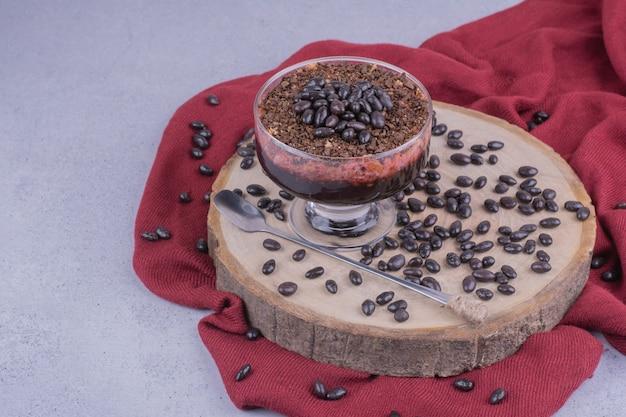 Une tasse de café avec des grains de chocolat sur planche de bois.