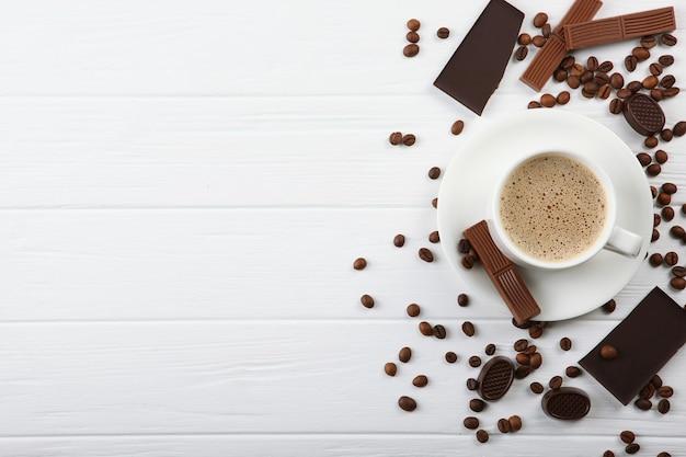 Tasse de café en grains et chocolat sur la table en gros plan