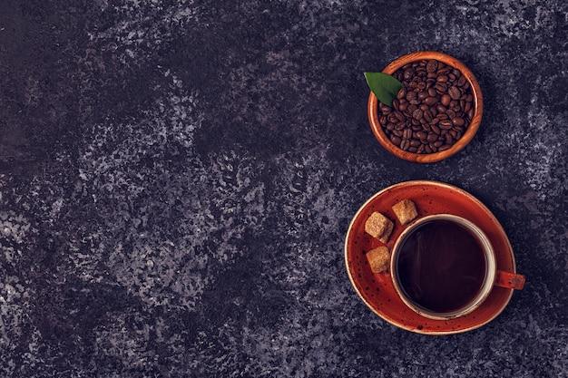 Tasse à café, grains, poudre moulue et sucre.
