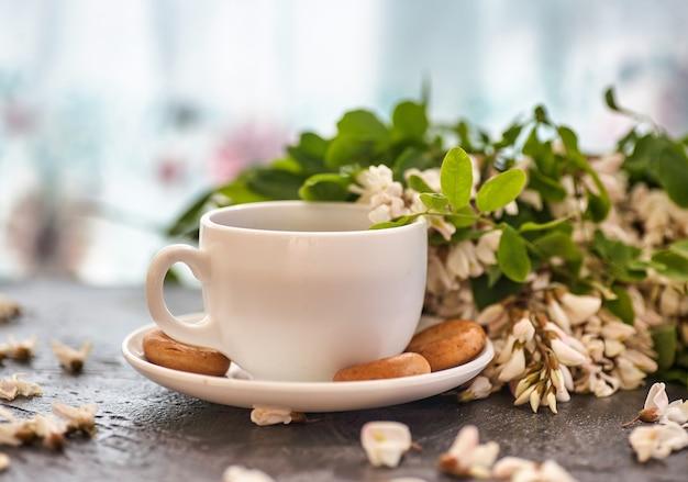 Tasse de café et gros plan d'acacia. une tasse de café et de fleurs d'acacia.
