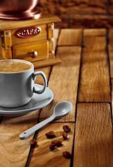 Tasse à café gros plan et moulin sur table en bois