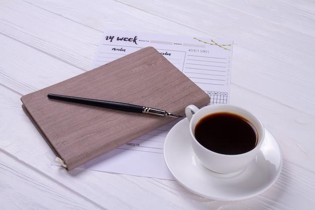 Tasse de café en gros plan avec stylo à encre et livre.