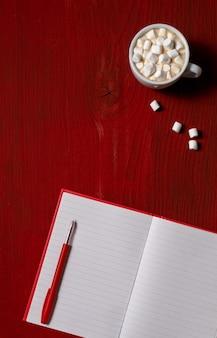 Tasse de café avec guimauve et note avec stylo sur bois rouge