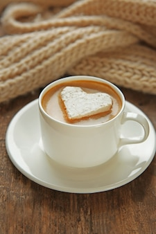 Tasse de café avec guimauve sur table en bois