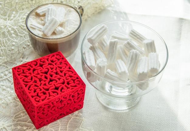 Tasse à café avec des guimauves, bol en verre avec des guimauves, boîte à anneaux rouge sur nappe en dentelle beige