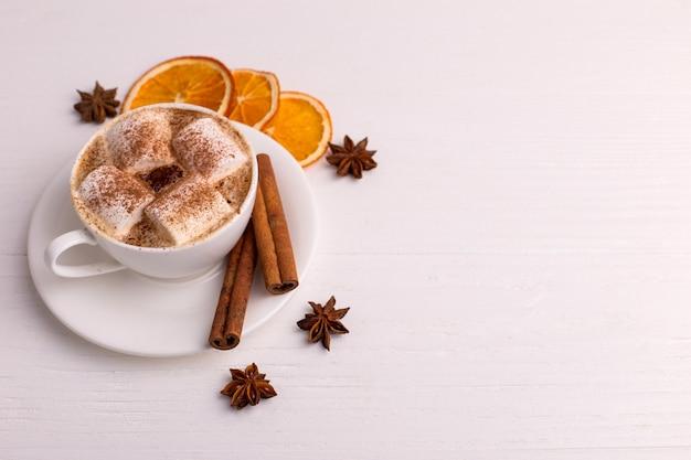 Tasse de café avec guimauves et cacao, feuilles, oranges séchées, épices, sur fond blanc. délicieuse boisson chaude en automne, ambiance du matin. fond