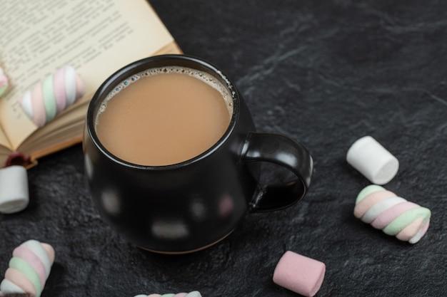 Une tasse de café avec des guimauves et un livre.