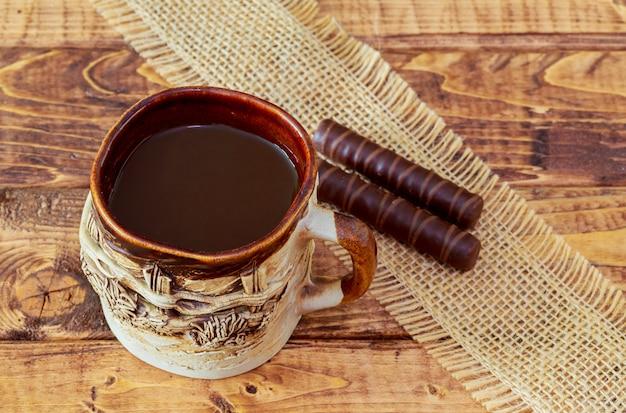 Tasse à café et haricots, bâtons de cannelle, chocolat sur fond de table en bois