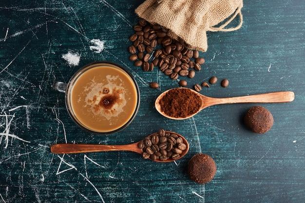Une tasse de café avec des haricots et des biscuits.