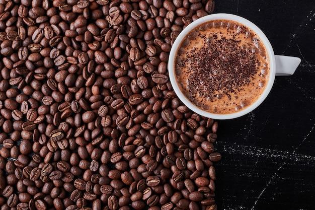 Une tasse de café sur des haricots bruns.