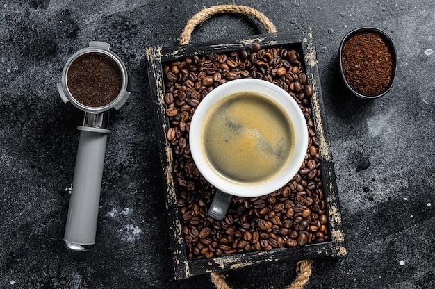 Tasse à café et haricots dans le vieux plateau en bois sur table noire. vue de dessus.