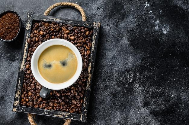 Tasse à café et haricots dans le vieux plateau en bois