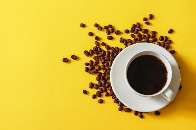 Tasse de café avec des haricots dispersés sur un fond jaune