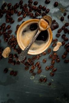 Tasse à café avec des haricots et du sucre sur métal vintage, copie espace, vue de dessus