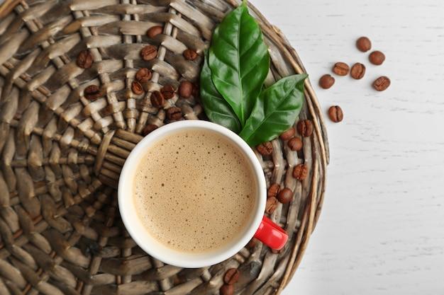 Tasse de café avec des haricots et des feuilles sur une surface en osier