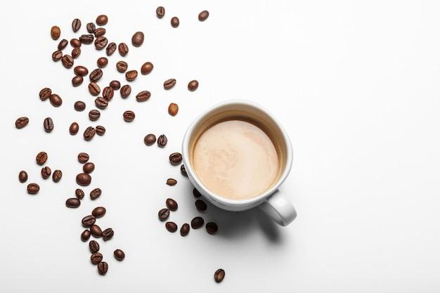 Tasse à café et haricots sur fond blanc