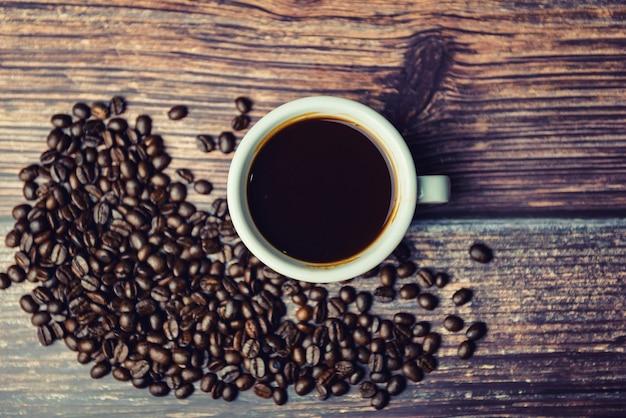 Tasse de café avec des haricots sur fond en bois