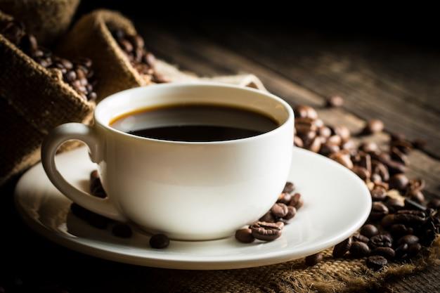 Tasse à café et haricots sur un fond rustique.