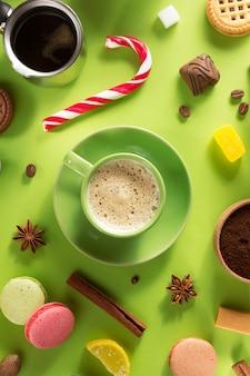 Tasse à café et haricots à la surface du papier vert