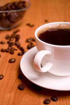 Tasse de café et haricots sur table en bois
