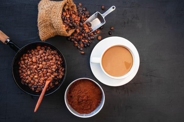 Tasse à café et haricots sur tableau noir. vue de dessus
