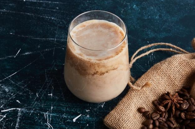 Une tasse de café avec des haricots sur la toile de jute.