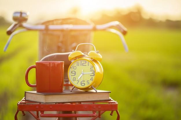 Tasse à café, horloge et livre posés sur le vélo classique de style japon rouge devant un champ de riz vert