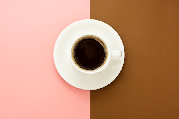 Tasse à café isolée sur table marron et rose. mise à plat du café noir abstrait