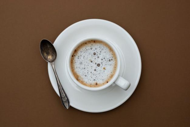 Tasse à café isolée sur table marron. vue de dessus, boisson au café noir à plat avec copie espace.